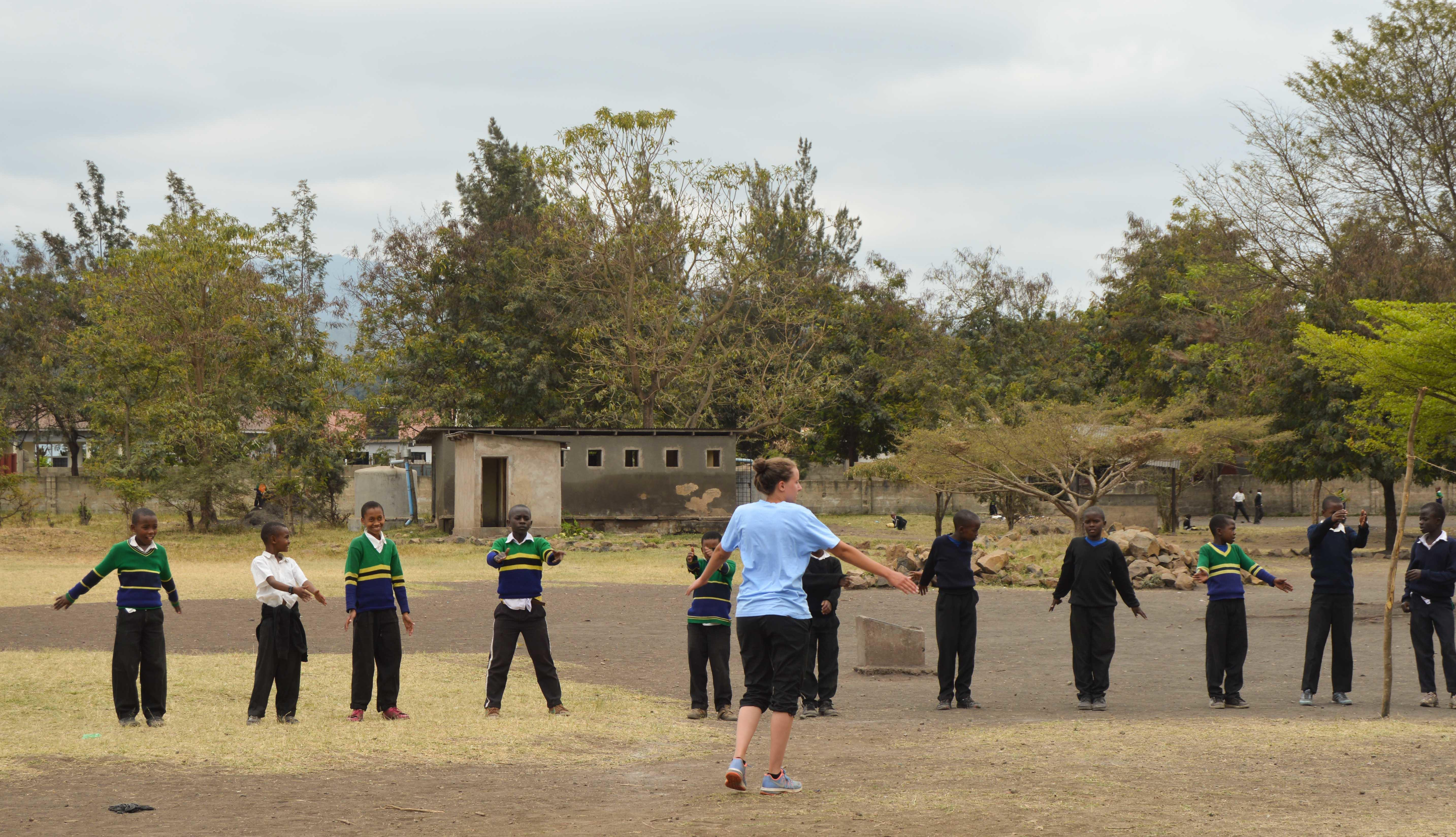 A sports instructor does a quick warm up with students during her volunteer sports coaching in schools in Tanzania